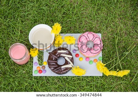 Donut and milk in the garden. - stock photo