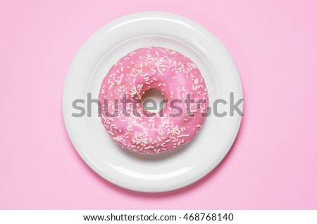 Donut covered with icing in plate, top view. Photo in a pink color scheme