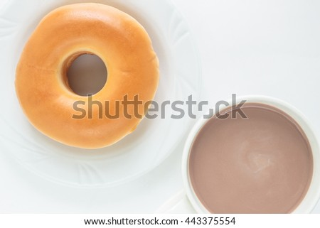 donut on white plate and cup cocoa drink top view on white background.