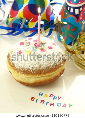 Donut with candle for birthday and confetti - stock photo