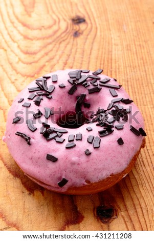 donut with pink frosting on wooden table