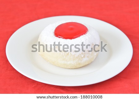 Donut with strawberry jam on white dish. - stock photo