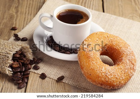 Donut with sugar and cup of hot coffee on wooden table - stock photo