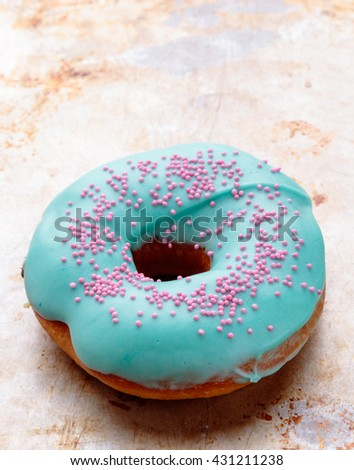 donut with turquoise frosting on steel plate - stock photo