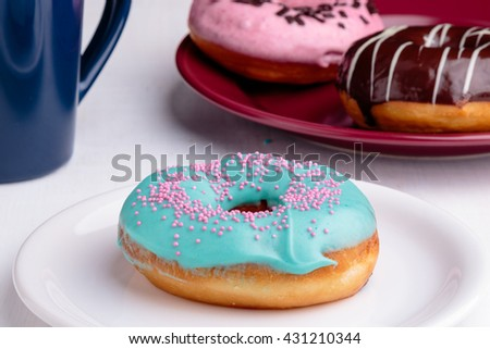 donut with turquoise frosting on white plate - stock photo