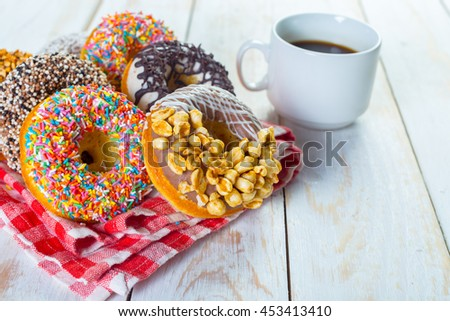 Donuts and coffee on a white wood background. - stock photo