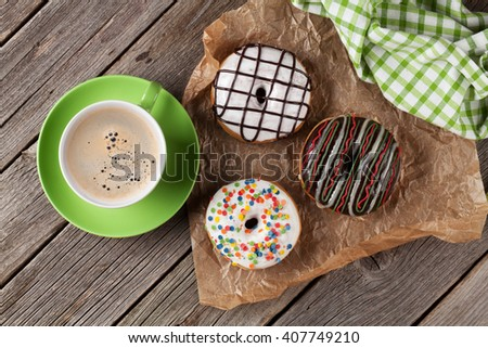 Donuts and coffee on wooden table. Top view - stock photo