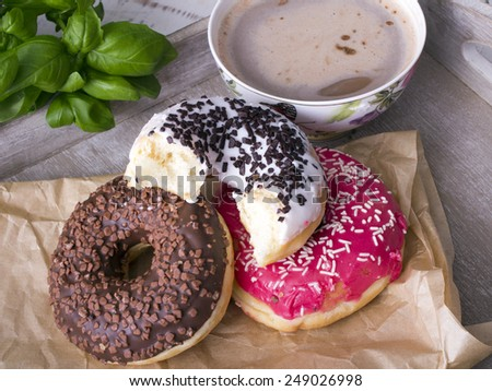 donuts and cup of coffee on wood background - stock photo