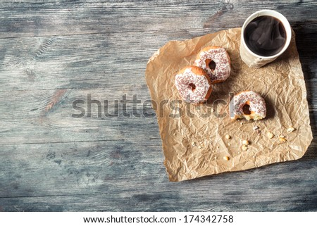 Donuts, coffee and wooden table background - stock photo