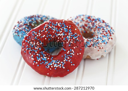 Donuts decorated with icing and sprinkles for fourth of July celebration. Selective focus with very little depth of field. - stock photo