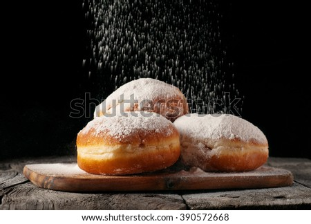 Donuts sprinkled with powdered sugar on wooden table on black background closeup. Food background - stock photo