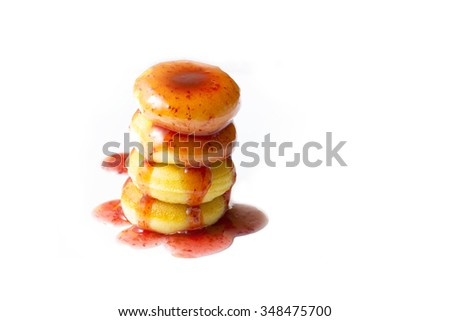 Donuts stacked and topped with syrup, strawberries on white background - stock photo