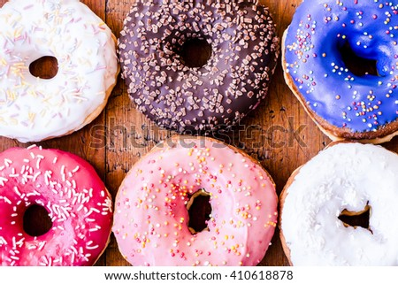 Donuts. Sweet icing sugar food. Dessert colorful snack. Glazed sprinkles. Treat from delicious pastry breakfast. Bakery cake. Doughnut with frosting. Baked unhealthy round.  - stock photo