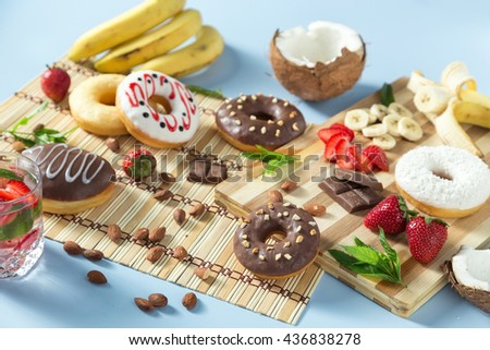 Donuts with chocolate, coconut and strawberry. Served on the wooden board. Decorated with strawberry, banana, coconut, almond, chocolate and mint. With lemonade and ice. Horizontal image.