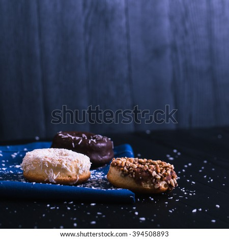 donuts with different powder on a black wooden background