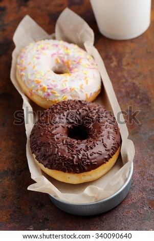 Donuts with frosting and sprinkles on a rustic table - stock photo