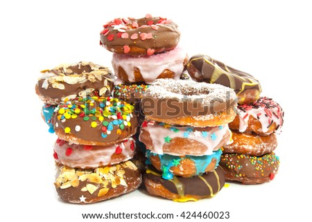 Donuts with sweets on a pile isolated over white