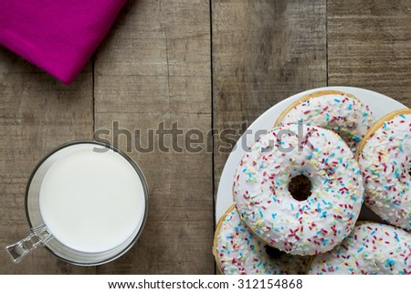 Donuts with white glaze and colorful sprinkles on rustic table - stock photo