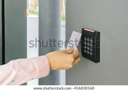 Door access control with a hand inserting keycard to lock and unlock door - stock photo