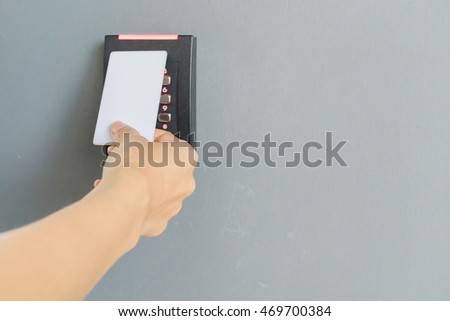 Door access control with a hand inserting white key card to lock and unlock door on gray background. Security concept.