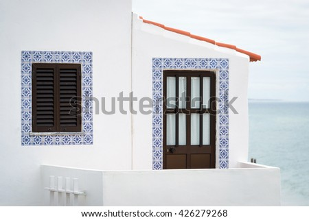 door and window of house decorated with traditional Portuguese tiles - Azulejos, Portugal - stock photo