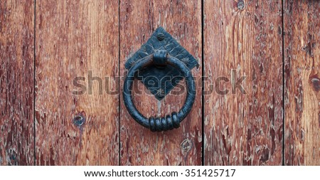 Door handle-knocker on the old wooden door