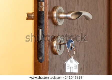door handle with inserted key in the keyhole and house icon on it - stock photo