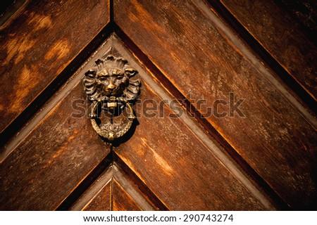 Door knocker on the old wooden door - stock photo