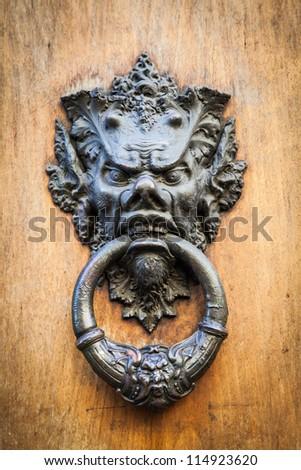 Door knoker on an old wodden door in Tuscany - Italy - stock photo