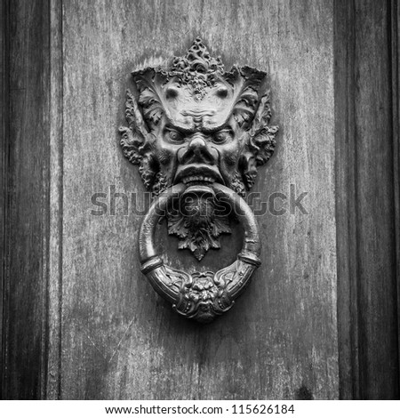 Door knoker on an old wodden door in Tuscany - Italy - stock photo