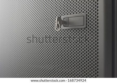 Door  metallic black of server rack cabinet. The key is inserted into the door lock. Side lighting and  shallow DOF - stock photo