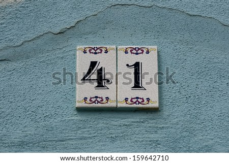 Door numbers on a painted wall. - stock photo