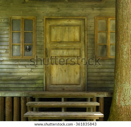 Door of wooden house with stairs in the forest