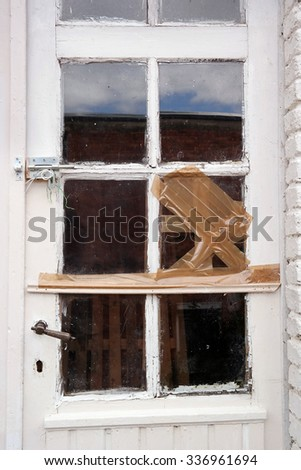 Door window with broken glass pane temporarily repaired with tape - stock photo