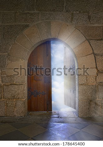 Door with arch opening to a beautiful cloudy sky - stock photo