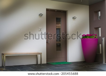 door with pink flower pot , bench, and mat  - stock photo