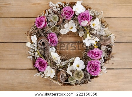 Door wreath made of artificial flowers and autumn plants on wooden background - stock photo