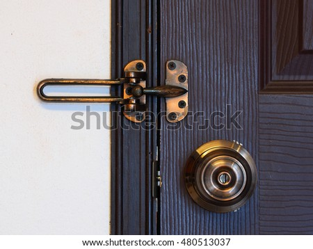doorknob and bolt or latch with wooden door - security , warm tone