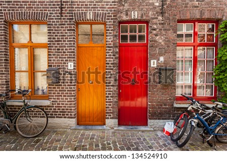 Doors of old houses and bicycles in european city. Bruges (Brugge), Belgium - stock photo