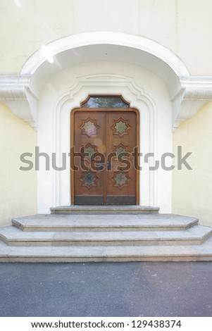 Doorway to run down old home with white painted wall - stock photo
