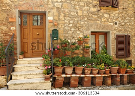 doorway to the tuscan house with lots of flowerpots, Italy - stock photo