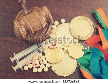 Doping in sport. Gavel, gold medals and tablets with syringes on table - stock photo