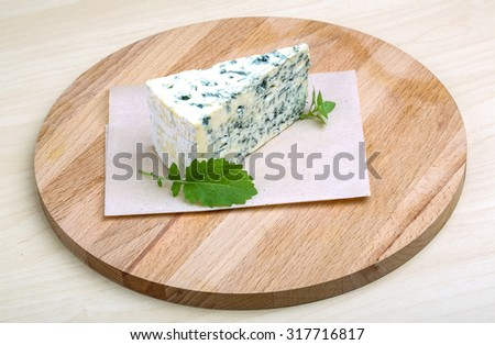 Dor Blue cheese with basil on the wood background