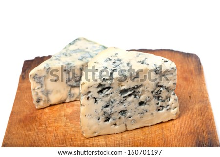 Dorblu cheeses on old wooden kitchen board. On white background