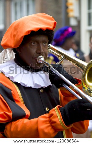 DORDRECHT, THE NETHERLANDS - NOVEMBER 18: Man dressed as Black Piet playing trombone in a parade celebrating the arrival of Santa Claus in Holland on November 18, 2012 in Dordrecht, Netherlands. - stock photo