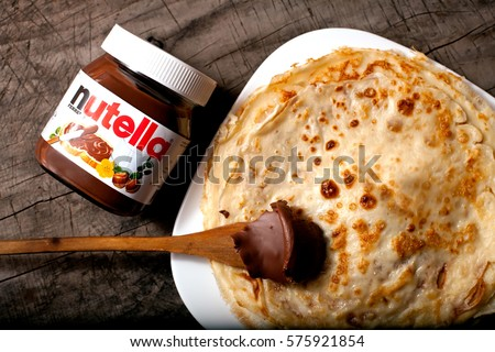 DORKOVO, BULGARIA - FEBRUARY 08, 2017: Close up Nutella jar and pankcakes over wooden vintage grey background.Nutella is the brand name of a chocolate hazelnut
