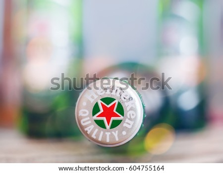 DORKOVO, BULGARIA - MARCH 13, 2017: Macro shot of Heineken bouttle over bar table, colorful club lights .Heineken Lager Beer is the flagship product of Heineken International