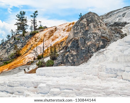 Dormant and active limestone deposits left by flowing, geothermal heated water at Mammoth Hot Springs in Yellowstone National Park, Wyoming. - stock photo