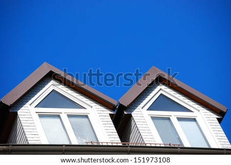 Dormer There are two dormers and a blue sky.  - stock photo