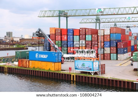 DORTMUND, GERMANY - JULY 16: Containers are loaded in Dortmund Port on July 16, 2012 in Germany. It is the largest canal port in Europe and had shipped almost 3 million tons of freight in 2007.